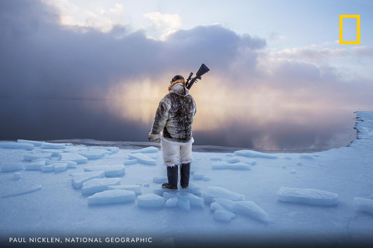 An Inuit hunter stands on the edge of the Arctic's shrinking sea ice in this powerful image by photographer Paul Nicklen.