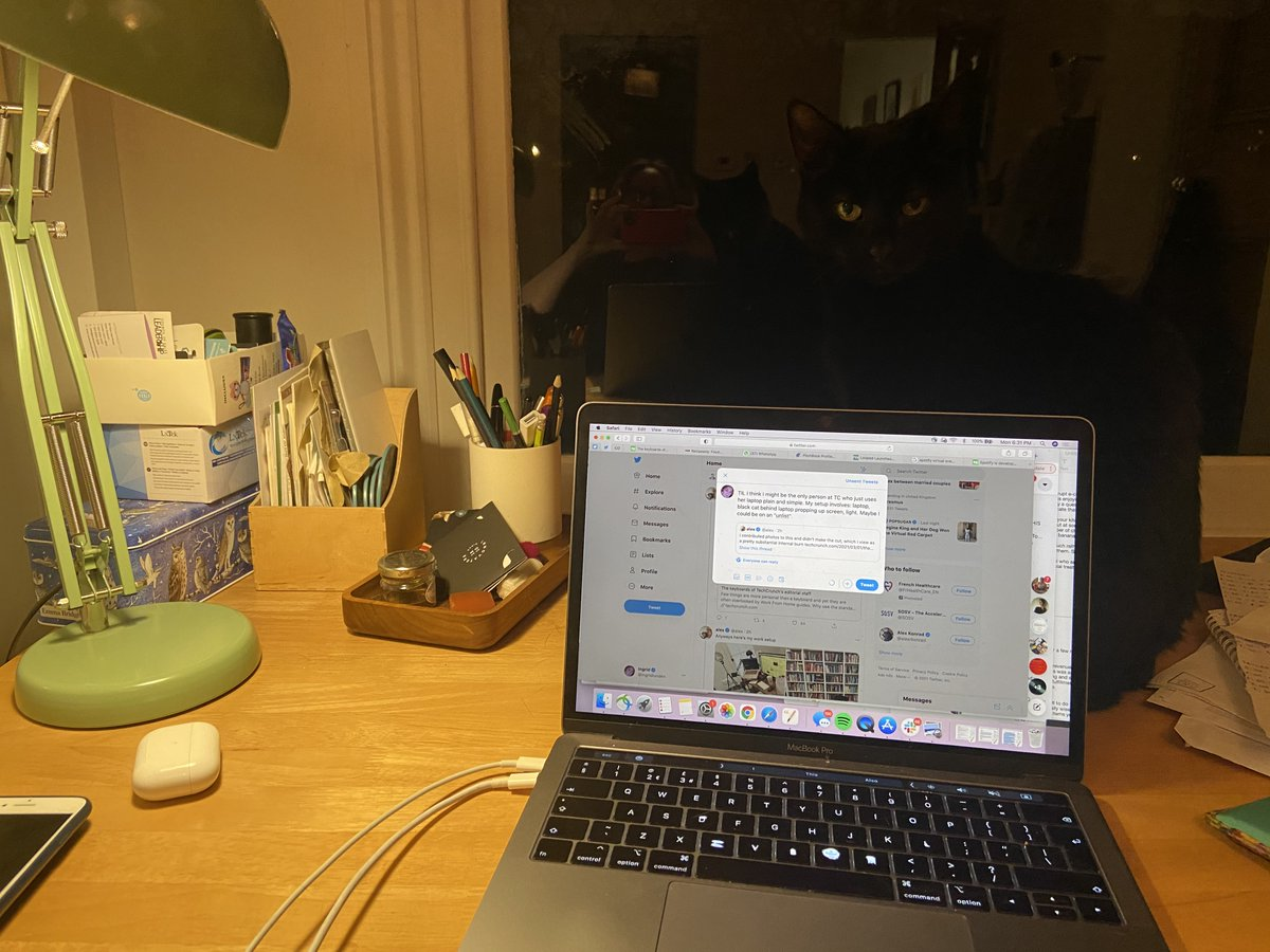 """TIL I think I might be the only person at TC who just uses her laptop plain and simple. My home office setup involves: slightly messy desk, laptop, 2 phones, AirPods, black cat behind laptop propping up screen, light. Maybe I could be on an """"unlist""""."""