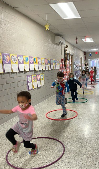 "Coach White has 1st grade using hula hoops  to Hop on Pop and ""jump rope""  -- all while wearing their pajamas!  #sosschoolvb #sosvbgr1rockstars #readacrossamericaday #drseussday #makeamess #hoponpop #catinahat #happybirthday"