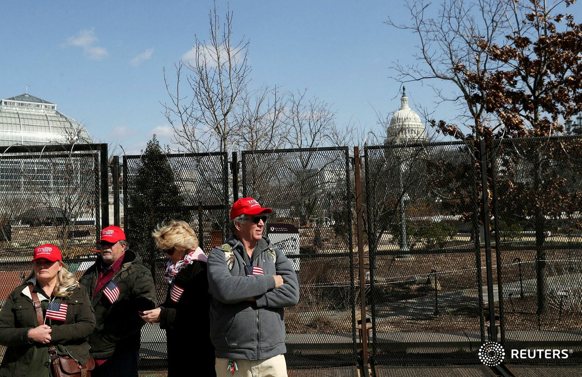 From left, Karyn Carson, John Carson, Lois Houser and Matthew Giannini, supporters of former President Donald Trump, stand near the security perimeter outside of the U.S. Capitol Building, hoping to see evidence of an inauguration of former President Trump. Photo by @LeahMillis