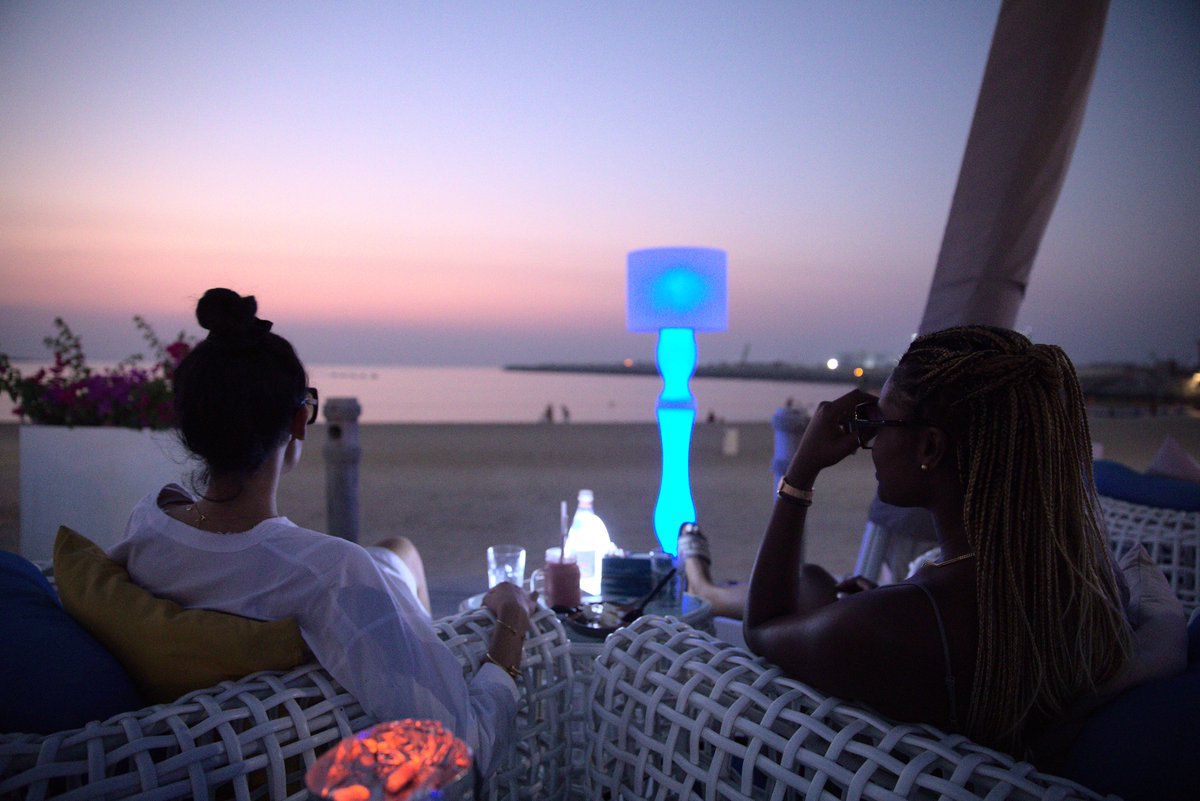 #SmokyBeach's dim-lit lights, laid-back ambience, delightful dishes & ice-cold beverages keep you hooked till you catch the last waves of the day!🌊  When are you dropping by for a #weekend beach fix with your bestie?  #LaMerDubai #DineIn #Sunset #Unwind #BeachVibes #hookahlounge