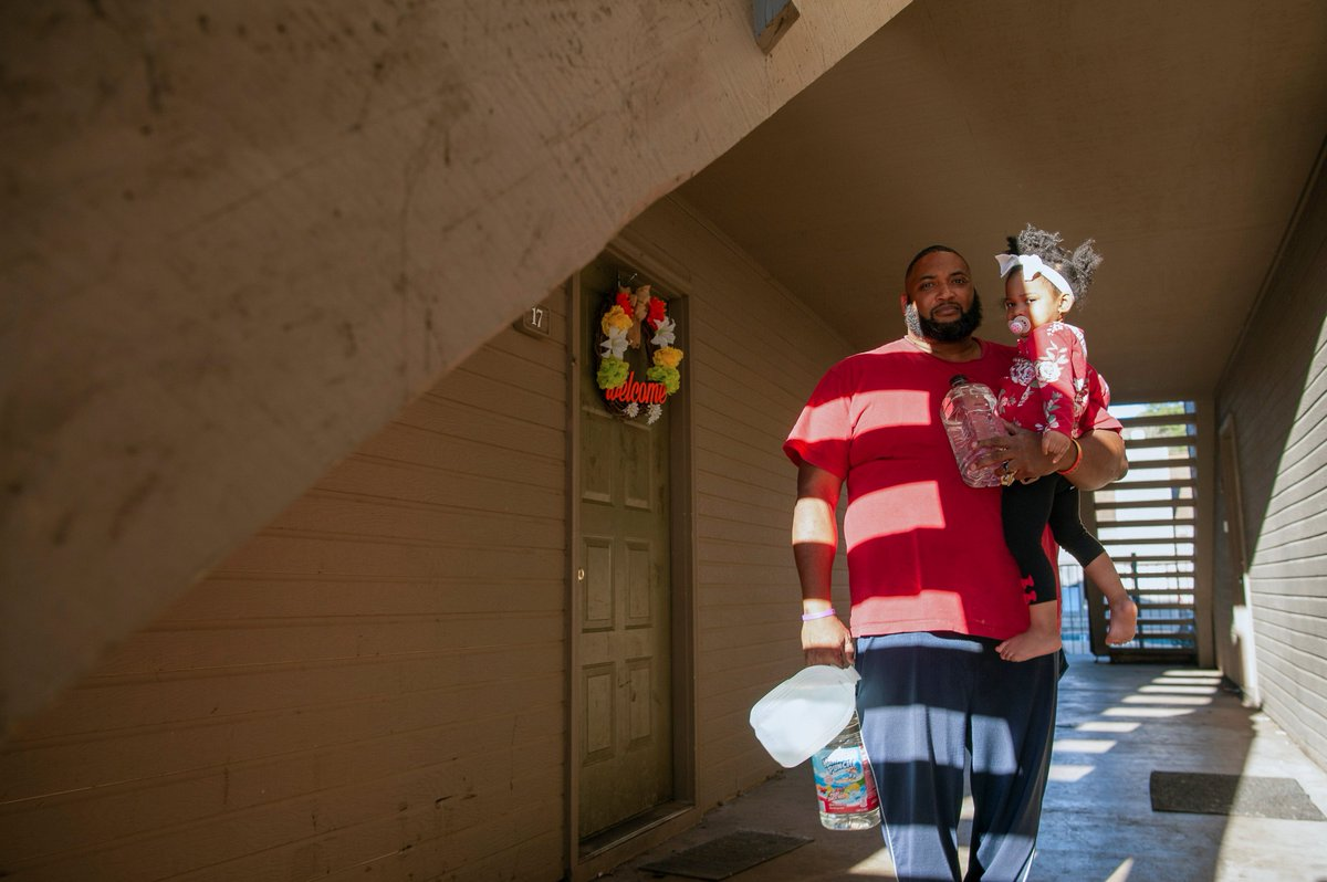 In Jackson, Mississippi, Kevin Dudley carries his daughter and bottles of water to his apartment after a recent bout of cold weather caused large numbers of water outages, some going into their third week.  📷 Rory Doyle / Reuters