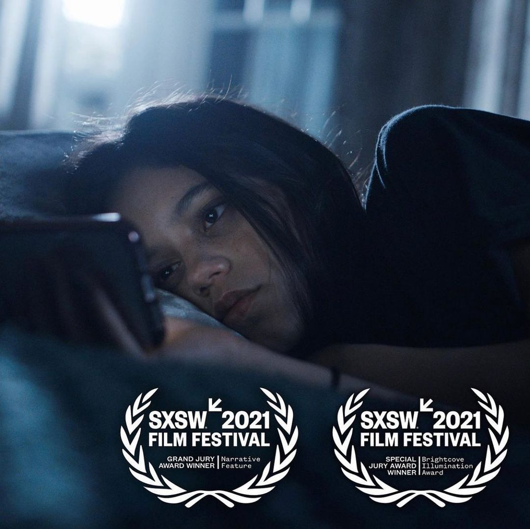 Jenna as Vada in a still from the film, lying on her bed reading her phone. The image has festival laurels printed on it, for the Grand Jury Award winner and the Brightcove Illumination Award for director Megan Park