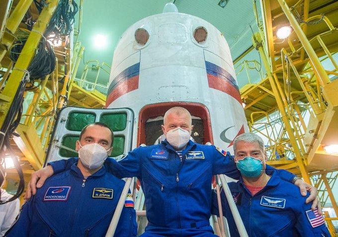 Astronaut Mark Vande Hei of NASA and cosmonauts Novitskiy & Dubrov in blue flight suits with Soyuz spacecraft
