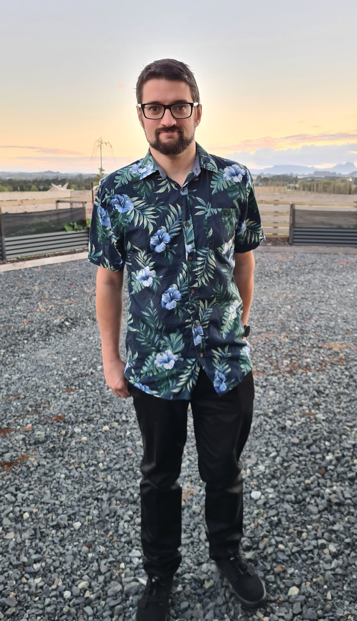 A picture of me in a dark blue and green patterned shirt, and black shoes and pants, wearing black framed glasses.  I have short brown hair, and a trimmed beard.  I am standing against a background with the sun just coming up