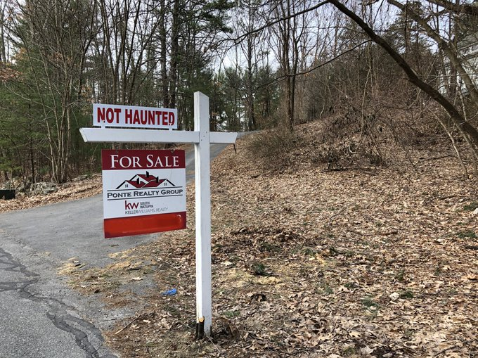 "Real estate for sale sign with ""Not Haunted"" rider"