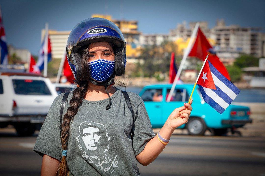 Una cubana sujeta una bandera de Cuba en la manifestación en contra del bloqueo económico impuesto por Estados Unidos.