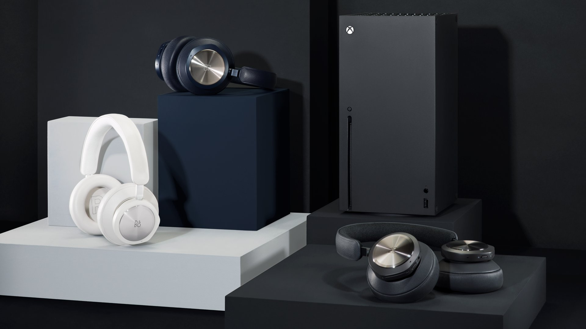 The three new Beoplay Portal headsets from B&O are arranged on like colors from left to right: Grey Mist, Navy Brass, and Anthracite. An Xbox Series X stands in the background.