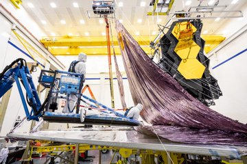 Technicians work together to lift up the James Webb Space Telescope's flattened sunshield in preparation for the folding process.