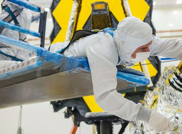 A technician hunches over a platform to carefully fold the sunshield layers of the James Webb Space Telescope.