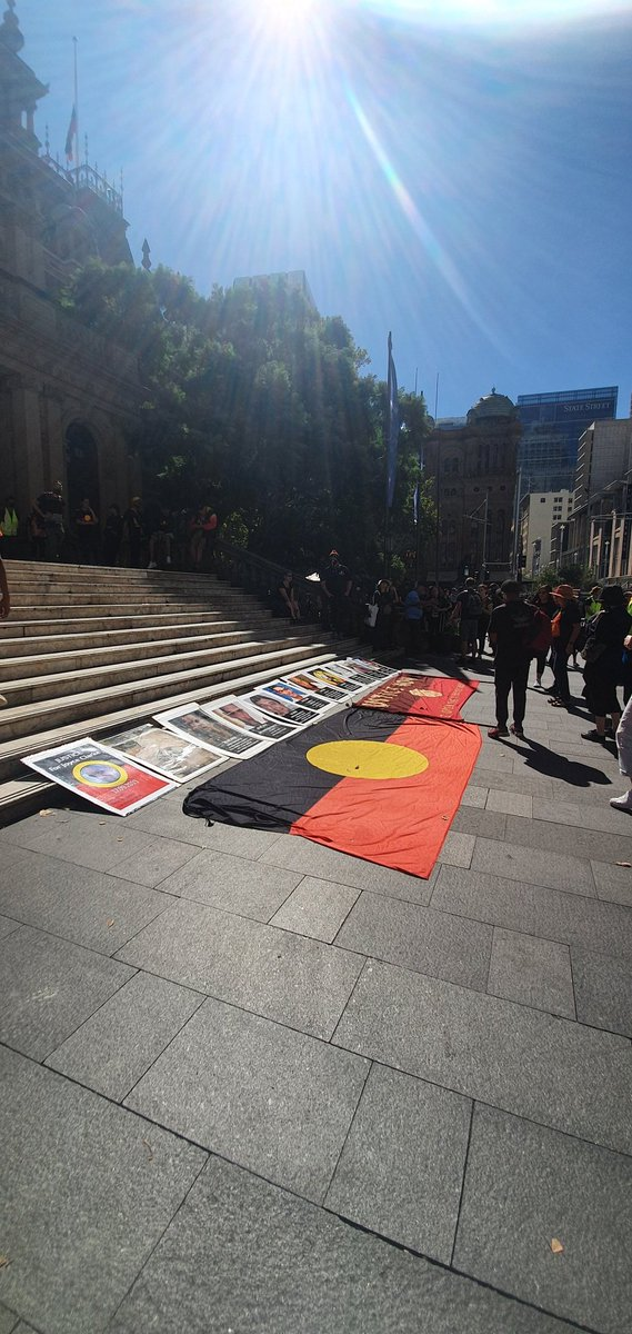 "An Aboriginal flag lays on the ground with the word ""justice"" in the centre. Posters of Aboriginal people killed by police lay in front. Town Hall steps in the background"