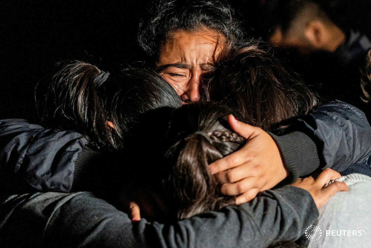 Asylum-seeking migrants' families from Guatemala embrace each other the moment after crossing the Rio Grande river into the United States from Mexico in Roma, Texas. Photo by Go Nakamura