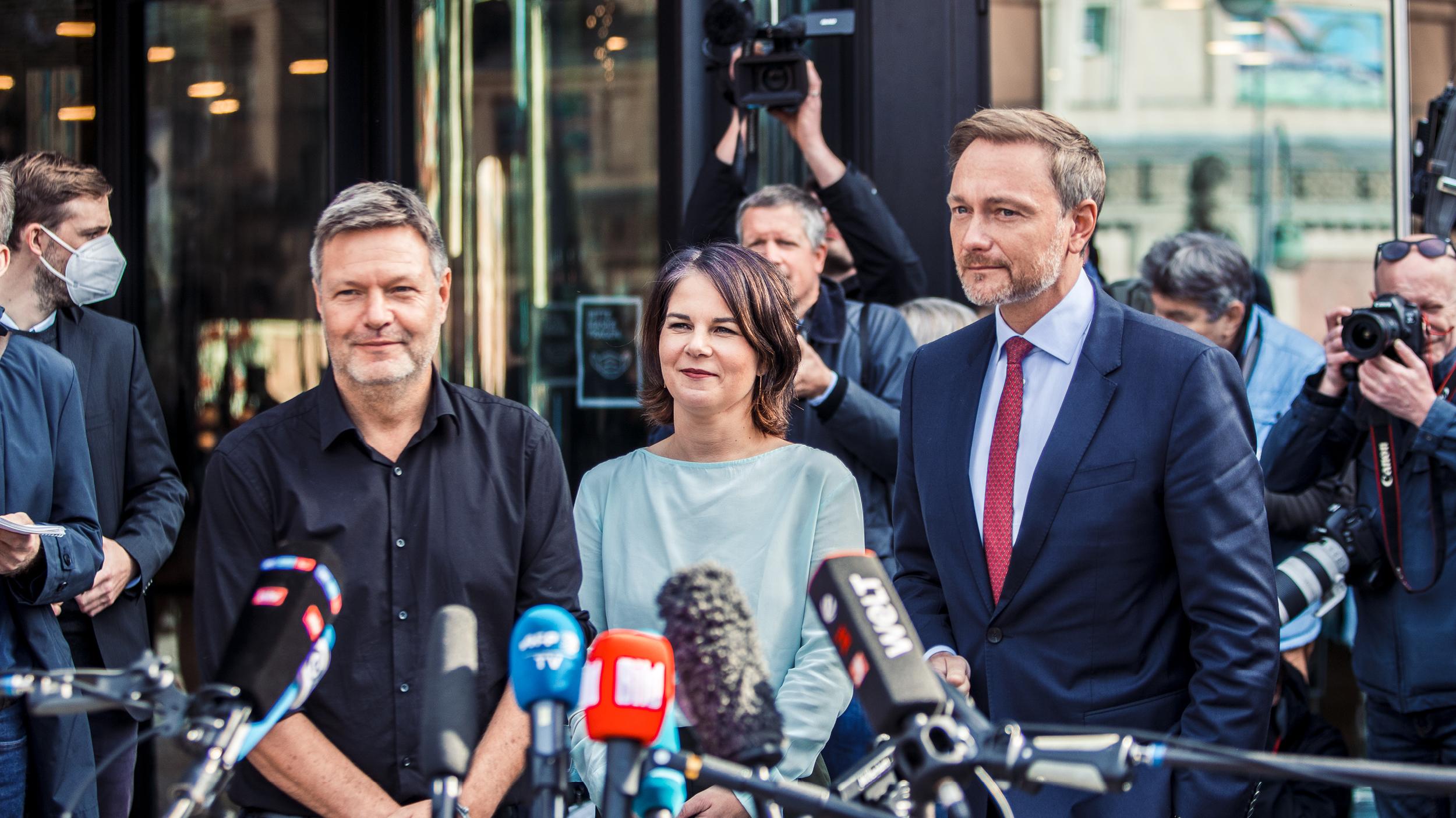 Von links nach rechts stehen Robert Habeck, Annalena Baerbock und Christian Lindner vor Mikrophonen. Sie sind umgeben von Journalist*innen, Kameraleuten und Fotograf*innen.