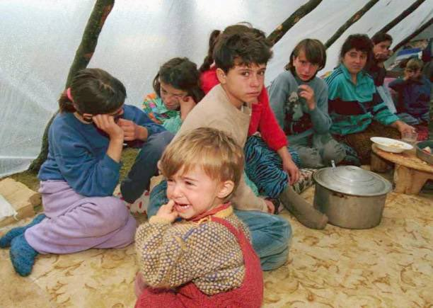 An ethnic Albanian boy cries in front of members of his family inside a plastic tent in the forest near the village of Damanek,south-west of Pristina, 03 October (1998). 𝙿𝚑𝚘𝚝𝚘&𝙲𝚊𝚙𝚝𝚒𝚘𝚗 𝚋𝚢 𝙼𝚕𝚊𝚍𝚎𝚗 𝙰𝚗𝚝𝚘𝚗𝚘𝚟/𝙰𝙵𝙿 #KosovoGenocide #KosovoWillNeverForget