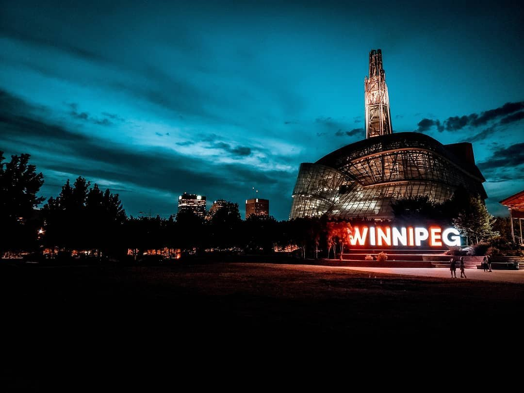 """An external shot of the Museum at dusk. A sign that reads """"Winnipeg"""" is illuminated in front of the Museum."""