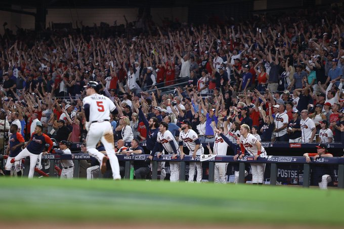 Freddie Freeman runs toward first base as the crowd in the stands at Truist Park and Freeman's teammates in the dugout all watch his home run sail out of the ballpark and begin to celebrate with their arms raised in the air.