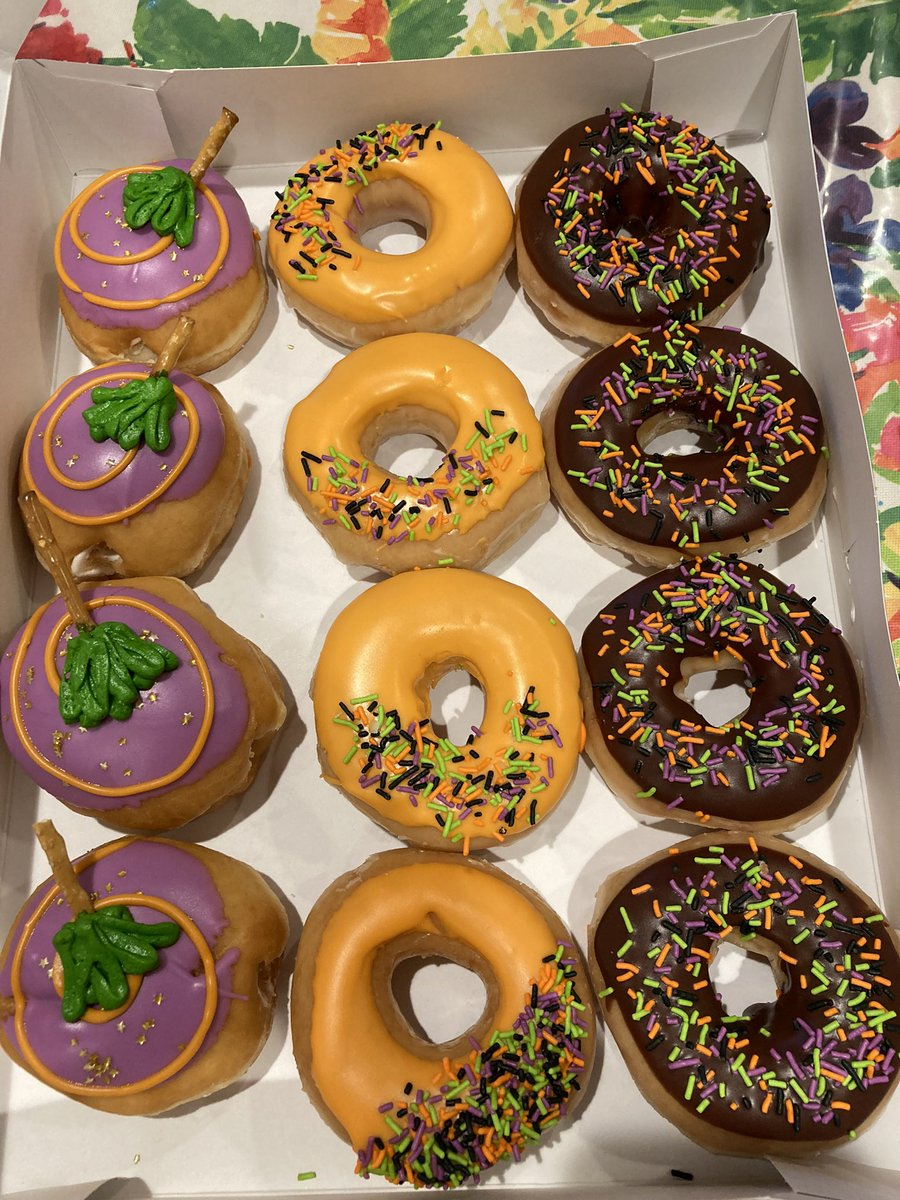 3 rows of Halloween themed donuts. One row is full of purple round filled donuts with a green witch broom theme. The other row is orange with purple, orange and green sprinkles. The last row is a chocolate donut with the same sprinkles.