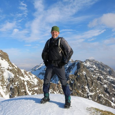 Image of Tom standing on a snowy mountain in Scotland.