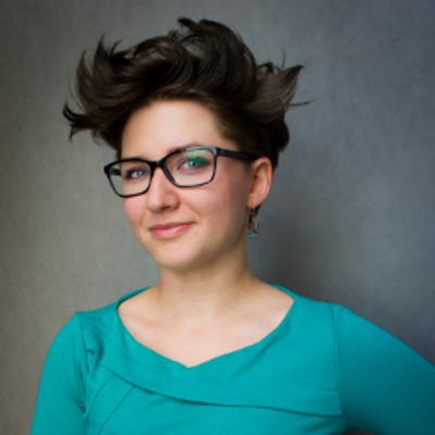 Natalia Panowicz of Codility is smiling into the camera and wearing a bright blue top against a dark grey background.