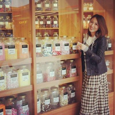 カラフルなお菓子の瓶が並ぶお店の前で笑顔の小椋久美子