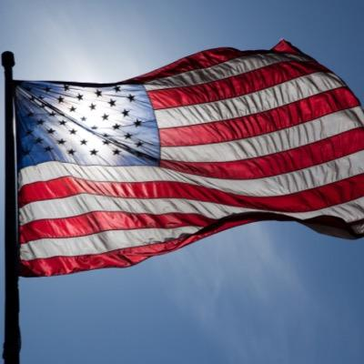 The American flag with the sun shining.