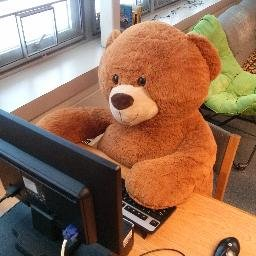 Giant brown teddy bear sitting at a computer in the Hamilton Middle School library.
