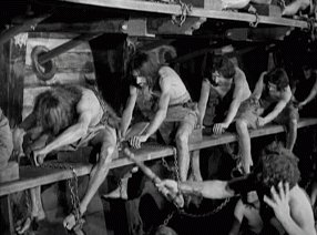 Half naked men in chains forced to row inside a ship