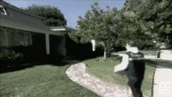 A delivery man walks up to a front yard of a home and kicks