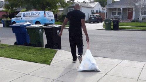 Man throwing away a bag of ...
